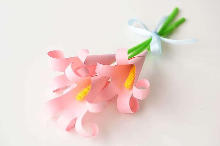 bunch of lilies, made from pale pink, rolled and folded paper, easter diy, with green and yellow, fuzzy wire stalks