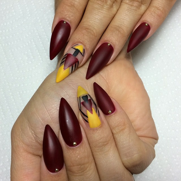 abstract symmetrical drawing, done in yellow, black and dark red, on dark wine-red manicure, long and sharp nails, tiny gold pearl details