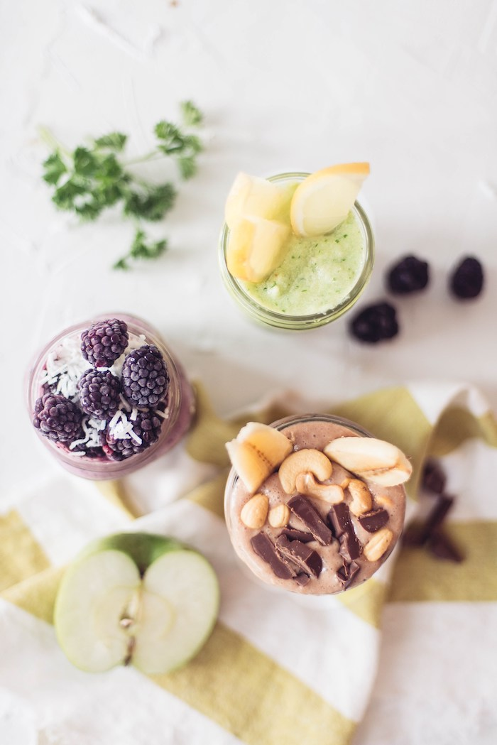 lemons and blackberries, cashews and banana slices, little milk chocolate bits, topping three different glasses, filled with blended drinks, protein shake recipes, halved green apple nearby