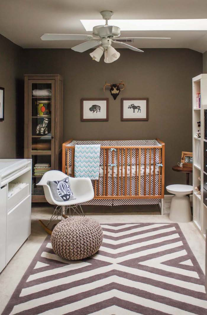 zebra cushion on white rocking chair, near pale brown wooden crib, with white and blue bedding, boys room ideas, brown walls and a ceiling fan lamp