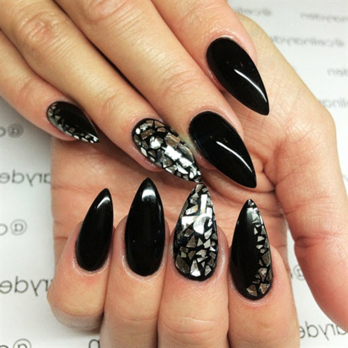 stylish smooth and shiny, black stiletto nails, some decorated with tiny, silver metallic shards