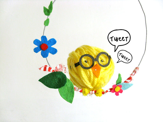 swinging chick ornament, easter crafts for adults, made from yellow ball of thread, with glasses and orange felt beak, stuck to a wire hoop, decorated with felt flowers