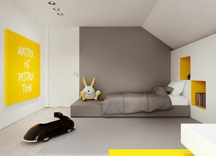 kid's white and grey bedroom, large black toy car, yellow canvas with white writing, stuffed toy and books