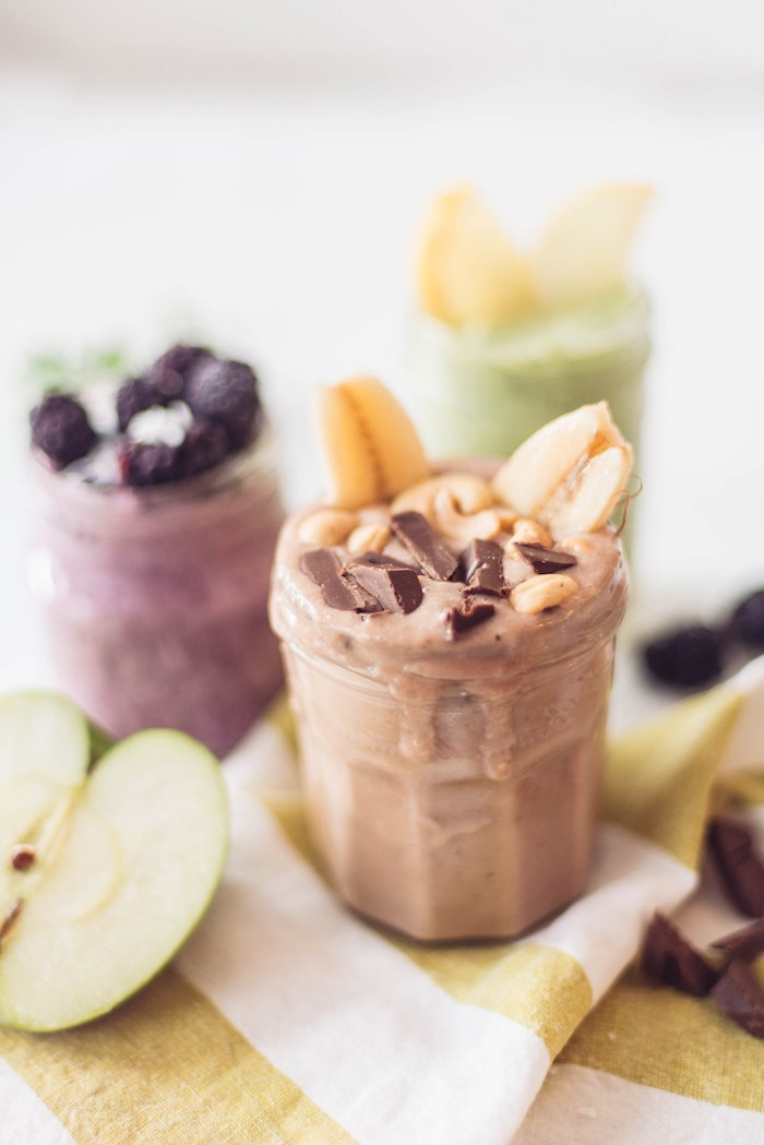 half of a green apple, near glass containing a beige smoothie, topped with banana slices, cashews and chocolate bits, protein shake recipes, more glasses in the background
