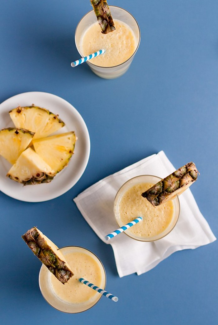 completed pineapple smoothie, poured into three glasses, each decorated with a pineapple slice, easy smoothie recipes, more pineapple chunks in a plate
