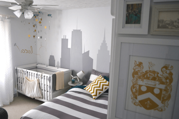 bed with striped duvet, in dark gray and white, near white and gray baby crib, wall mural depicting a city scape, painted in gray, various yellow motifs