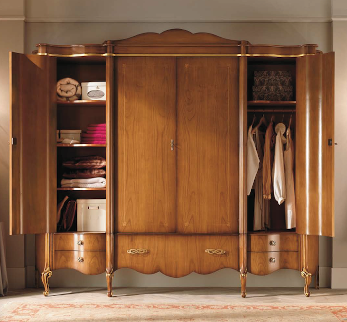 brown closet with four doors, made from wood, with engraved details, and ornate handles, two doors are open, to reveal clothes, storage boxes and blankets, classical wardrobes