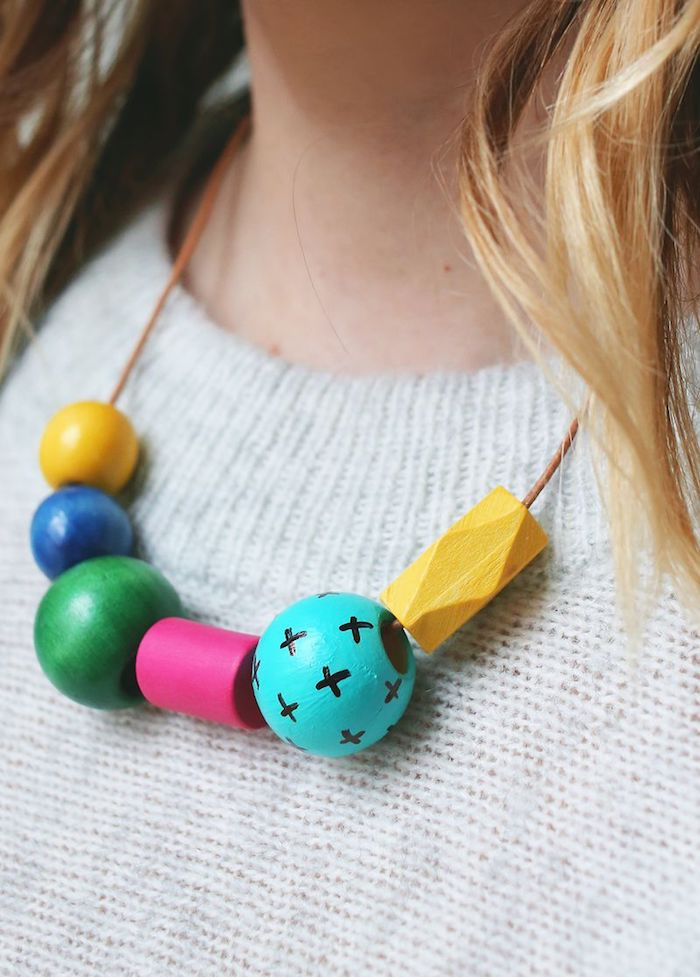 handmade necklace with wooden beads, in different shapes and colors, some decorated with hand-drawn patterns, mothers day gifts, on blonde woman's neck