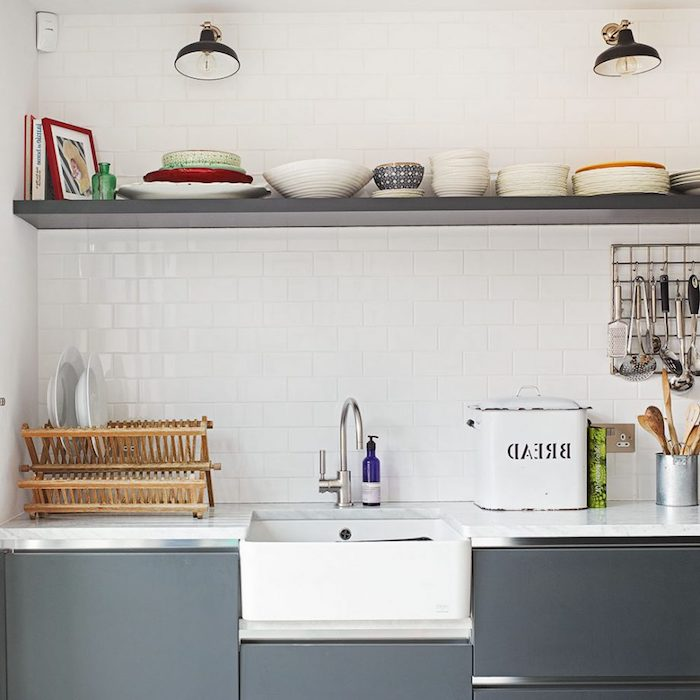 bread box with vintage design, and wooden dish drying rack, on white counter, near modern sink, smooth dark gray cupboards, and a matching shelf with plates, rustic kitchen decorations