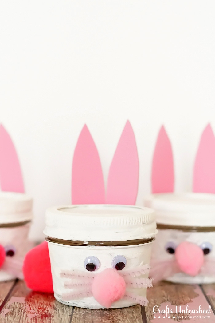 gift mason jars, painted white, and made to look like bunnies, placed on wooden surface, cute easter idea