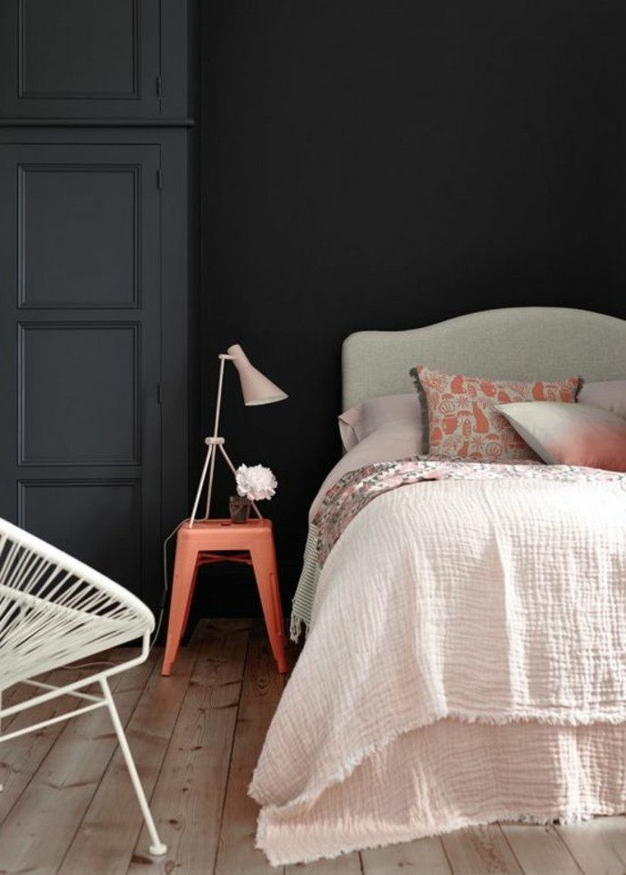 pastel pink and light gray bed, inside black or dark grey bedroom, light wooden floor, small bedside table, and white metal chair