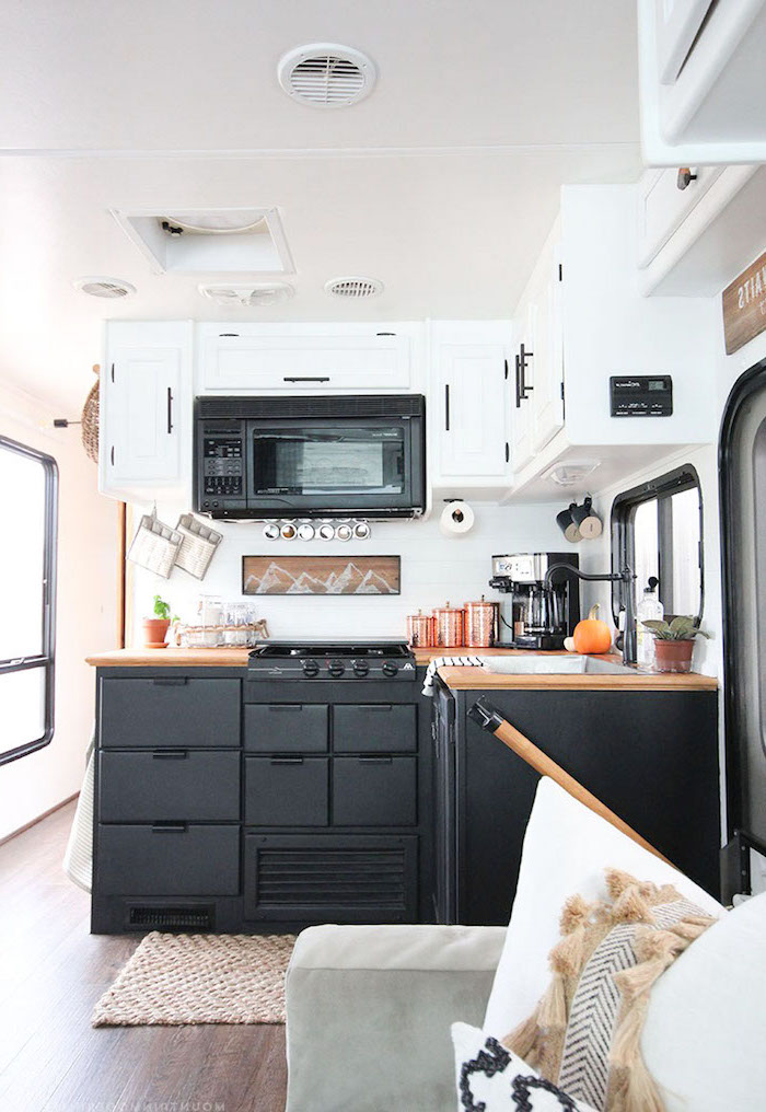 black vintage stove, and matching rustic kitchen cabinets, in room with white cupboards, light brown wooden floor, and pale gray sofa