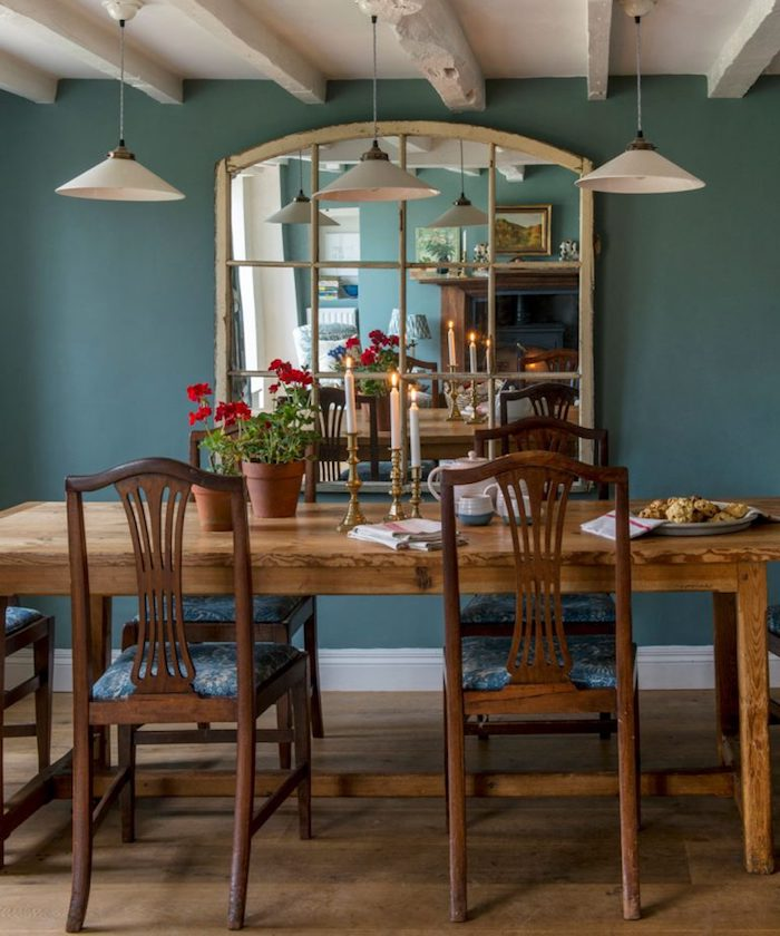 teal wall with large mirror, near wooden dining table, country kitchen décor, with three candles, flowerpots and crockery, white ceiling with wooden beams