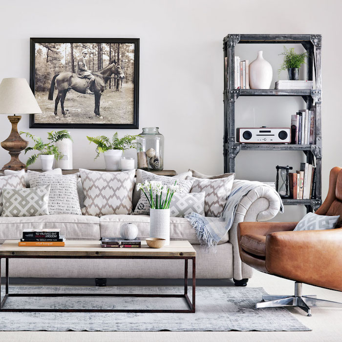 cream colored sofa, with lots of patterned cushions, in beige and white, living room color ideas, leather armchair and industrial-style rack