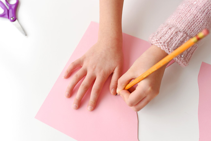 child in pale pink knitted sweater, tracing her hand with pencil, on sheet of pale pink paper, easter diy, scissors nearby