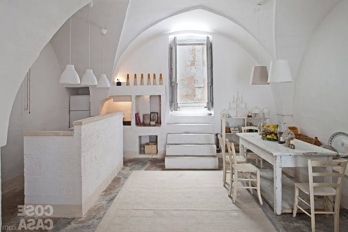 ivory and white kitchen, with shabby chic dining table, and cream-colored vintage chairs, vaulted ceiling and pale beige rug, country kitchen décor