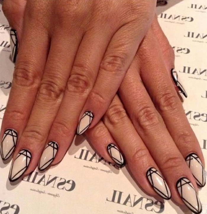 pale cream nail polish, on short stiletto nails, decorated with diamond shapes, outlined in black