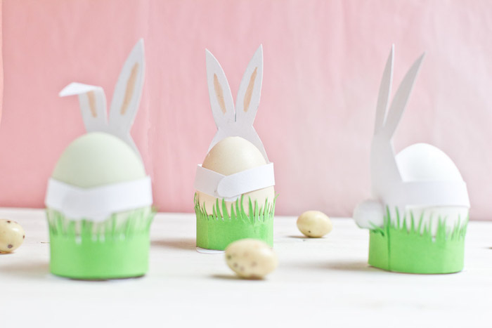 three off-white Easter eggs, inside paper holders, made from white and green card, shaped like bunnies, easter crafts for kids, quail eggs nearby