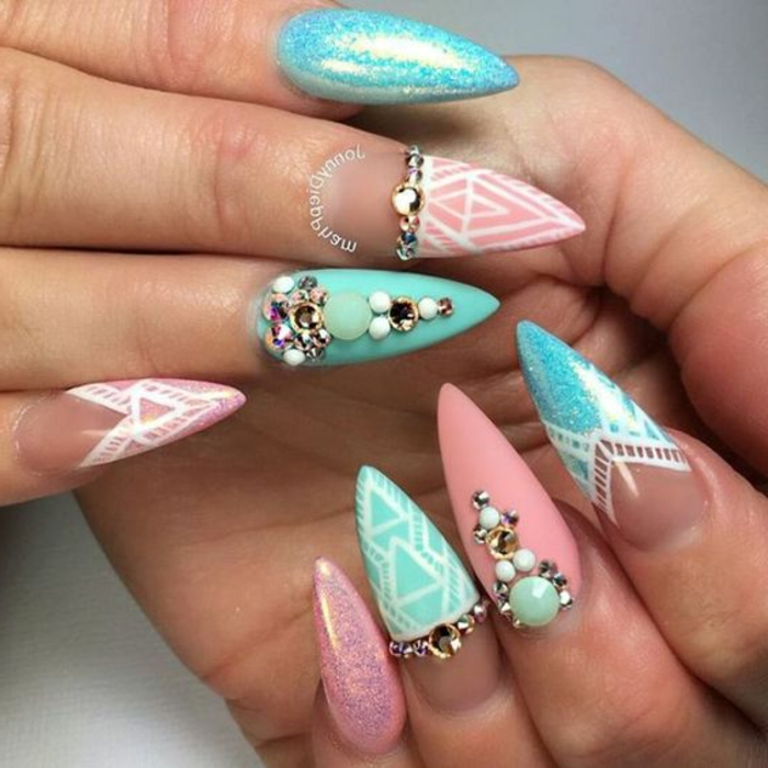 mix of pastel and glossy nail-polish, in white an pink, teal and turquoise, on stiletto acrylic nails, decorated with pearls and rhinestone stickers, and white hand-drawn dectails