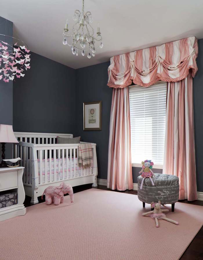 baby girl room décor, dark gray walls, pink and white striped curtain, white wooden crib, pale pastel pink carpet
