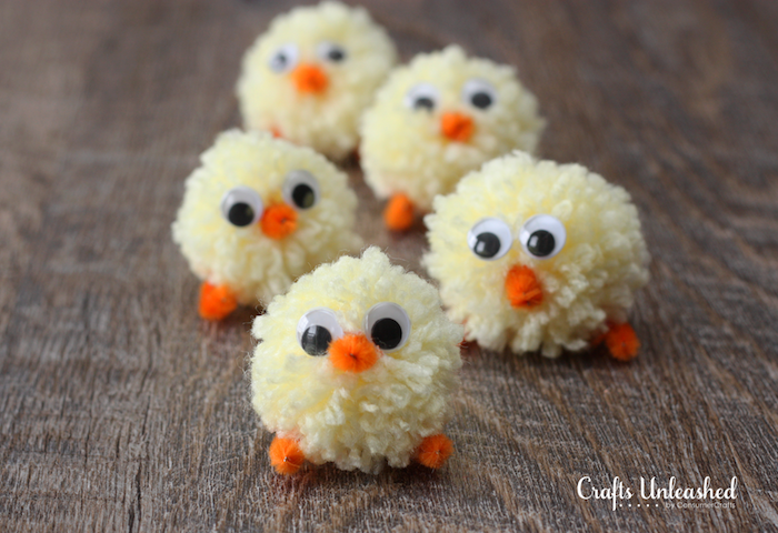 five chick decorations, easter crafts for kids, made from pale yellow pom poms, with tiny legs and beaks, made from orange fuzzy wire, and eye stickers