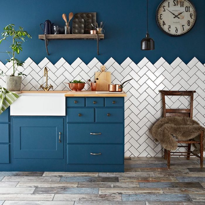 blue vintage rustic kitchen cabinets, in room with grayish brown laminate floor, dark blue wall half covered in white tiles, antique chair and wall closk