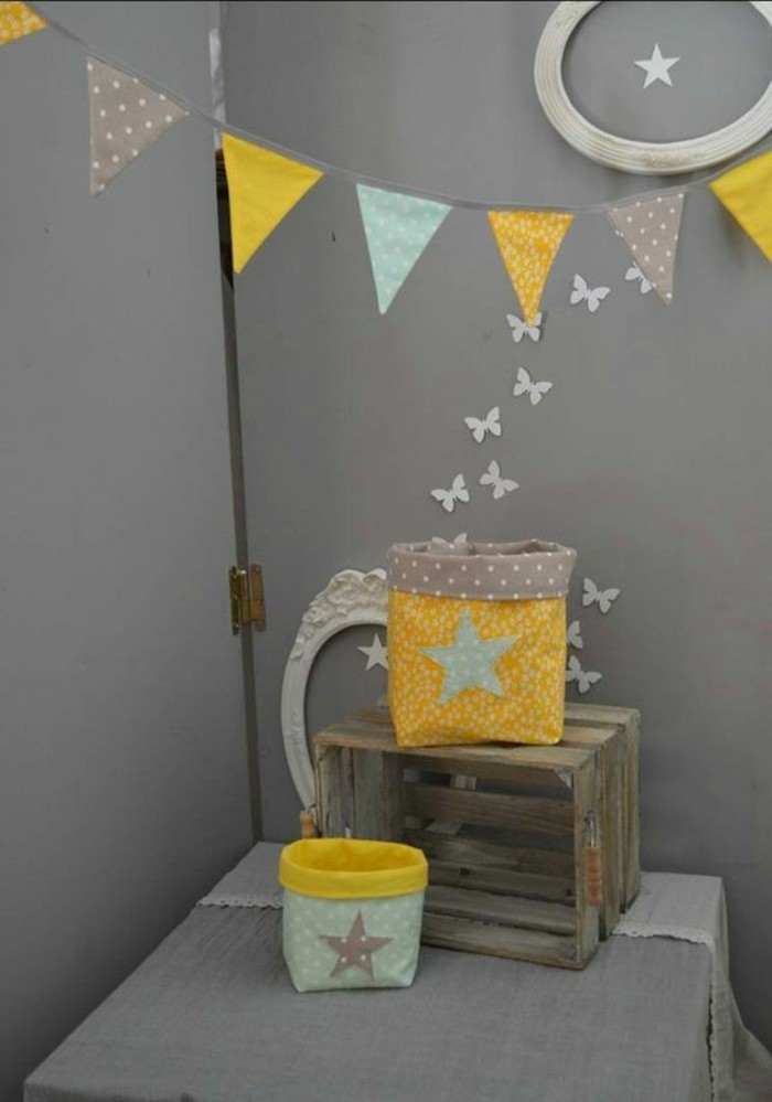 garland with patterned triangular flags, in yellow and light blue and gray, near wooden crate, and two fabric pouches, on table covered in gray fabric, dark gray kitchen or dining room
