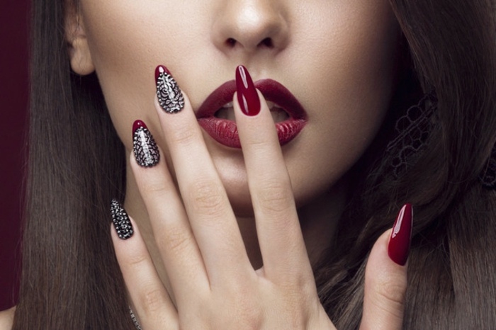 classic deep red nail polish, on long stiletto nails, decorated with silver glitter, worn by brunette woman, with matching re lipstick