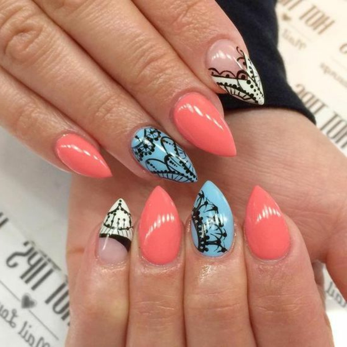 lace-like pattern, hand-drawn in black, on short stiletto nails, in coral pink, light blue and white, and clear nail polish