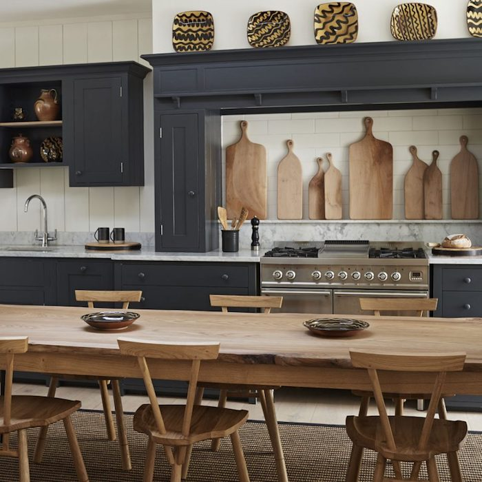 large wooden dining table, with six matching chairs, in room with dark gray, rustic kitchen cabinets, decorated with hand-painted wooden plates, and cutting boards