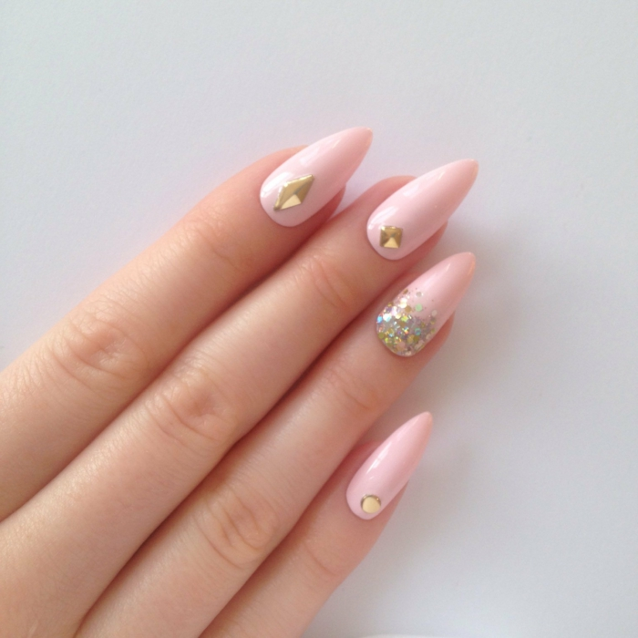 baby pink manicure, with iridescent glitter, and gem nail decals, stilleto nail designs