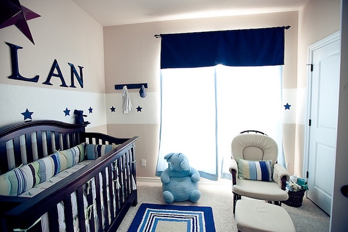 boy nursery, with beige and white walls, with star motifs, dark brown crib, dark navy details, pale blue elephant toy