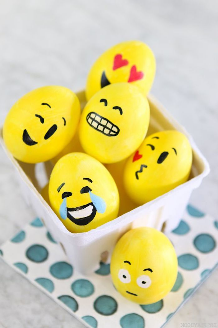 different funny faces or emojis, on easter eggs, painted in yellow, decorated with black, red and white paint, easter crafts for adults, inside white ceramic dish