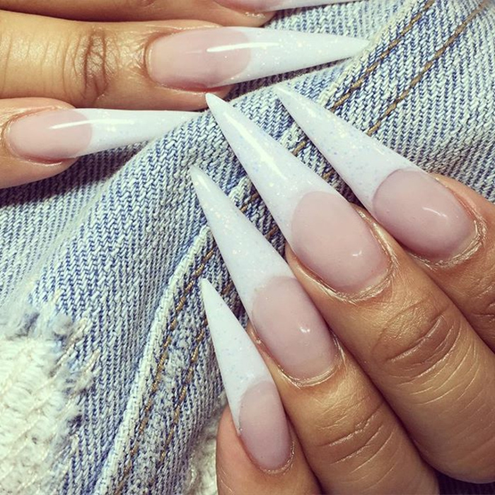 very long and sharp, french manicure-style claw nails, with extremely long white tips, covered with pale glitter