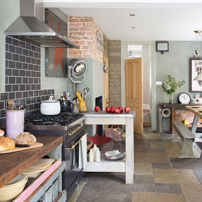 country kitchen décor, floor with brown and beige stone tiles, pale gray walls with brickwork details, shabby chic wooden counters, and an antique stove