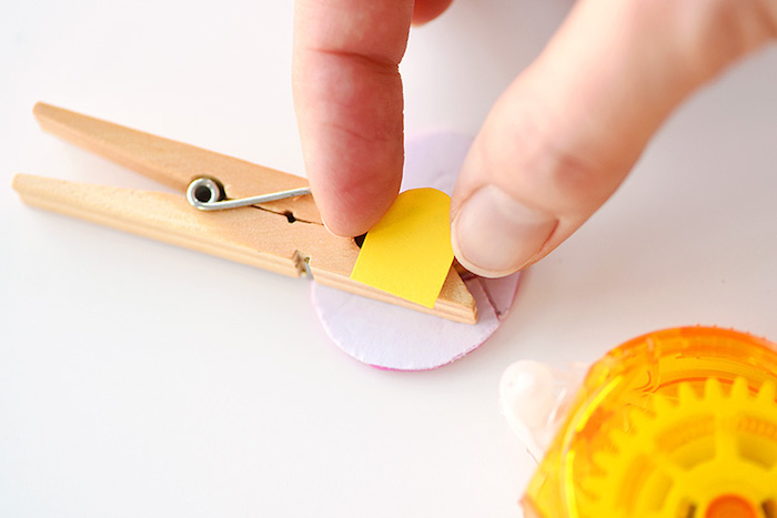 putting yellow cutout, on top of two-sided sticky-tape, stuck to a clothespin, and eggs-shaped card cutout, easter projects, fun and easy