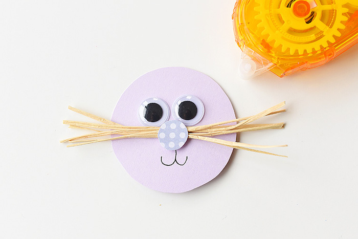 smiling cute face, with googly eye stickers, nose made from patterned paper, and straw-like whiskers, craft ideas for kids, yellow sticky-tape dispenser nearby