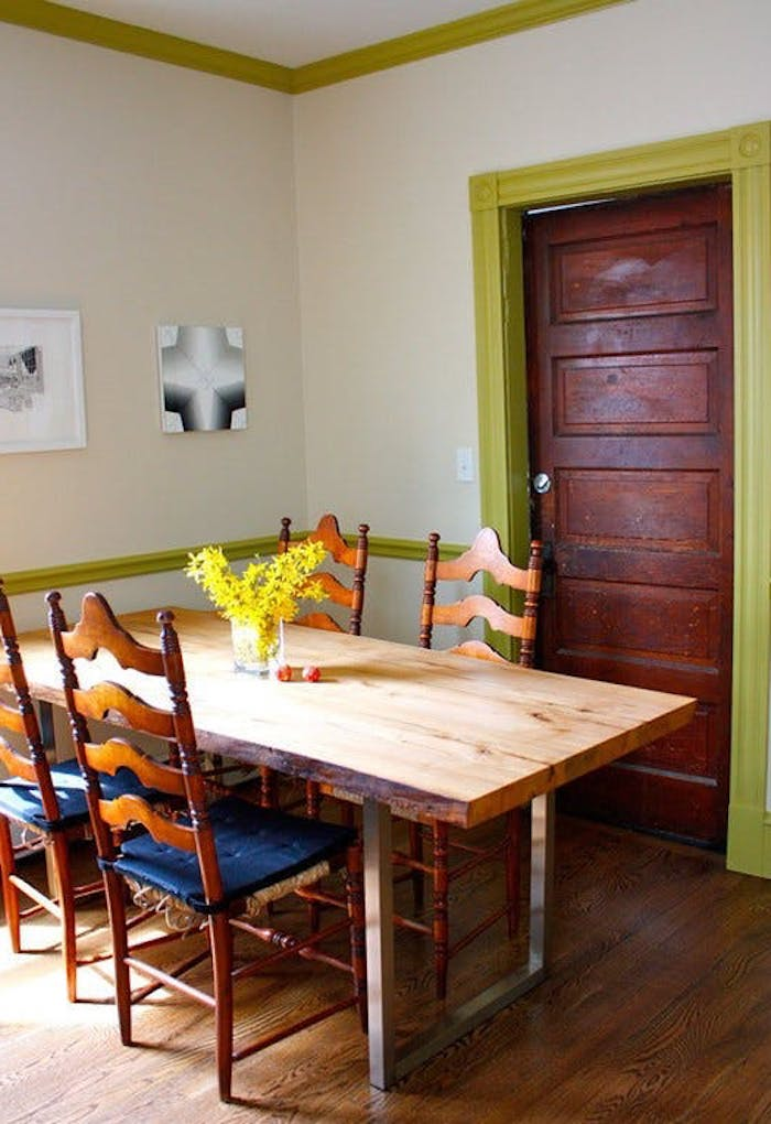 table made from natural wood and metal, with an industrial twist, and four retro chairs, in dining room with white walls, and pale green plaster details