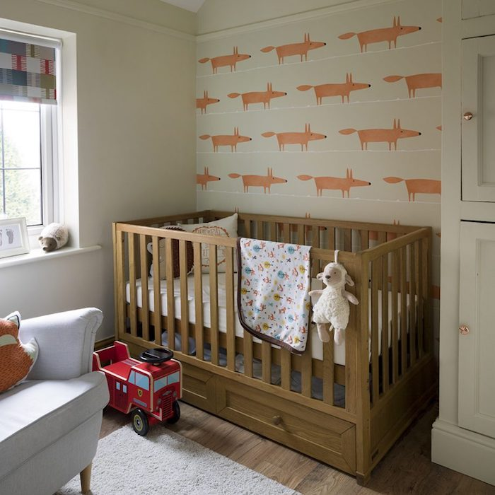 simple baby room, minimalist nursery ideas, off-white wallpaper with fox pattern, brown wooden crib, red fire-engine toy, and stuffed lamb doll