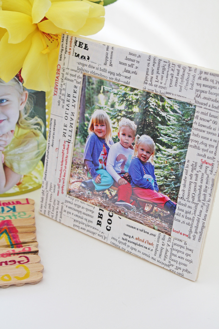 newspaper clippings collage, covering photo frame, containing image of three little children, mother's day gifts for grandma, yellow flower and more photos nearby