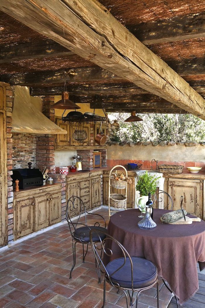 shabby chic rustic kitchen cabinets, with chipped beige paint, in a garden kitchen, with stone tiled floor, round table with purple tablecloth, three metal chairs, with dark cushions