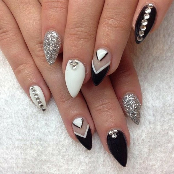triangular shapes on short stiletto nails, painted in black and white nail polish, decorated with silver glitter, and round rhinestone stickers