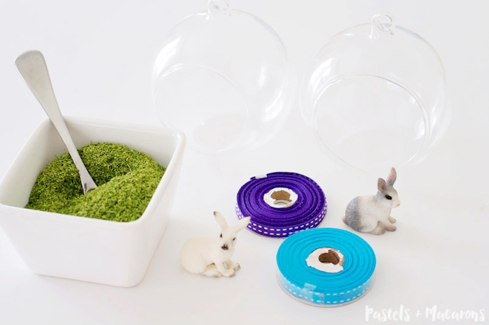terrariums made of glass, near white dish, filled with moss, easter projects, rolls of pale blue and purple ribbon, and two realistic rabbit figurines
