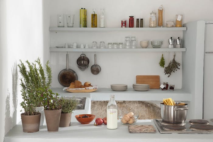 rustic kitchen in white, pale gray shelves, with cups and glasses, pans and condiments, several potted plants, milk and eggs, cooking dish with pasta