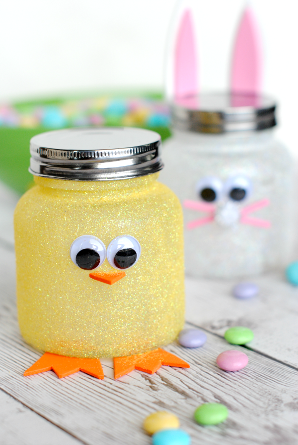 jars with metal lids, covered with yellow and white glitter, and decorated with felt cutouts, and eye stickers, to look like easter chick and bunny, easter crafts for adults, colorful candy nearby