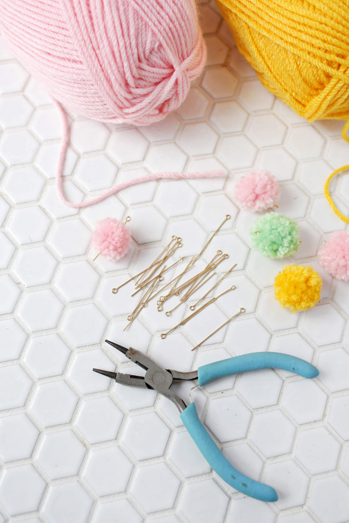 piercing pompoms with jewelry making pins, blue pliers nearby, woolen knitting tread, gift ideas for mom, how to make a bracelet