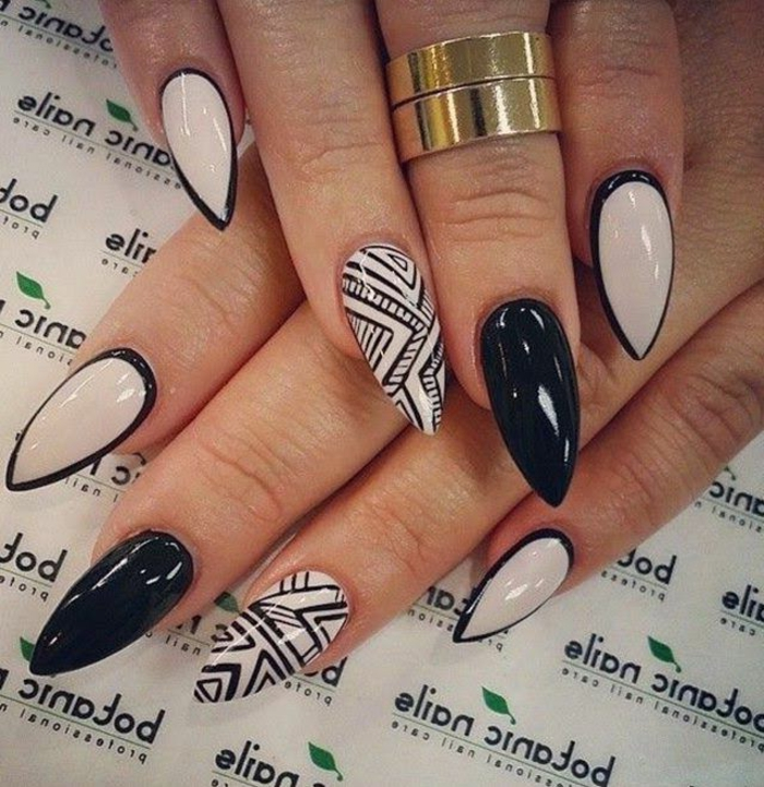 contasting white and black stiletto nails, black hand-drawn details, and frame effect, on two hands, with solid gold rings