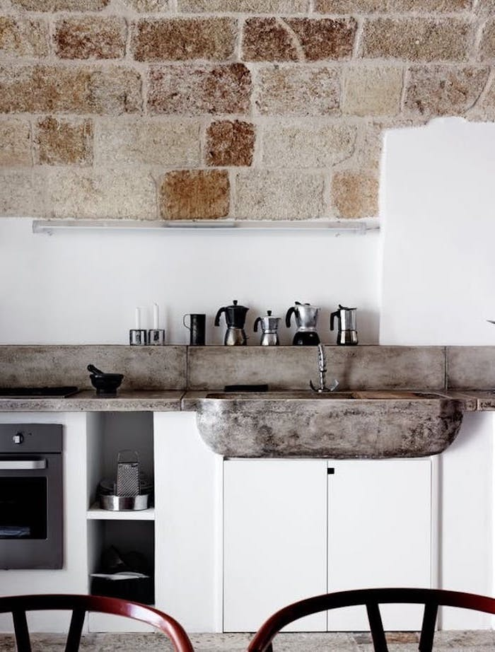 stone sink basin, and antique metal tap, in rustic kitchen, with white cupboards, and white wall with beige stone brick details, small assortment of coffee pots