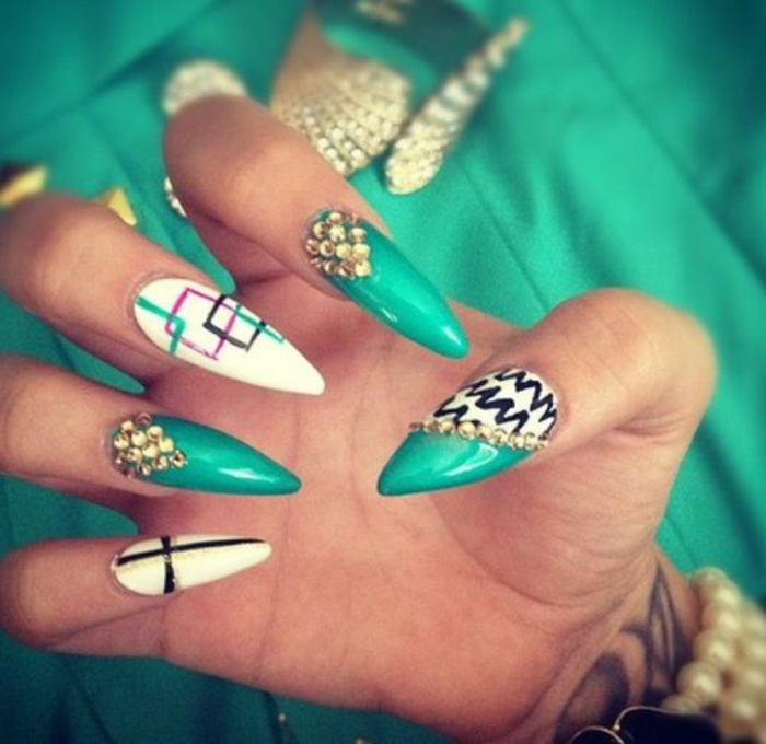 squares outlined in green, pink and black, on white and green long stiletto nails, decorated with hand-drawn scribbles, and little golden rhinestone stickers
