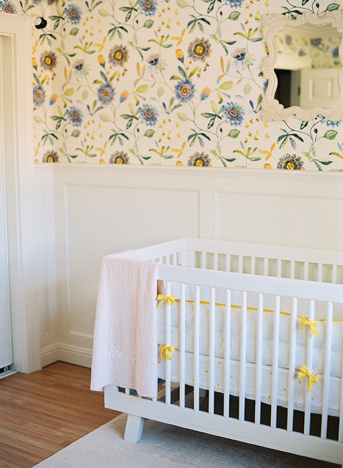 paneling in white, and white wallpaper, with flower pattern in yellow, blue and green, near white crib with yellow bows, decorative mirror in ornate frame